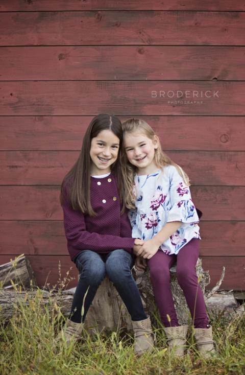 girls sitting on logs
